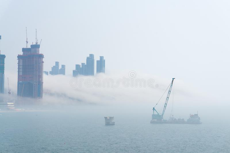 Thick large and heavy mist blow from the sea to the land and pass through ship near shore and skyscrapers. Inland and cover all other buildings in the area stock photography