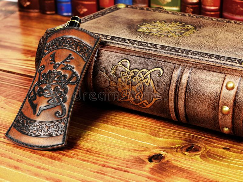 Thick leather book and pen holder lay down to the table with books royalty free stock images