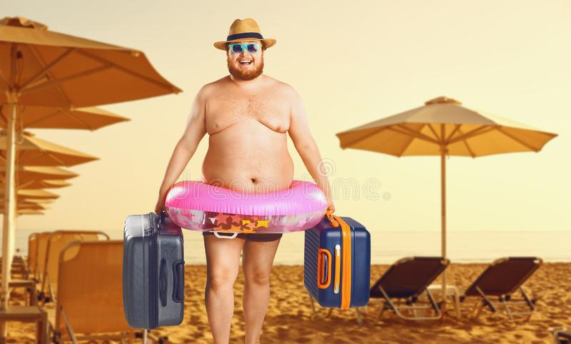 Thick man in a swimsuit with a suitcase and a rubber ring against the background of a summer beach. Funny summer holiday concept on the beach. Travels royalty free stock images