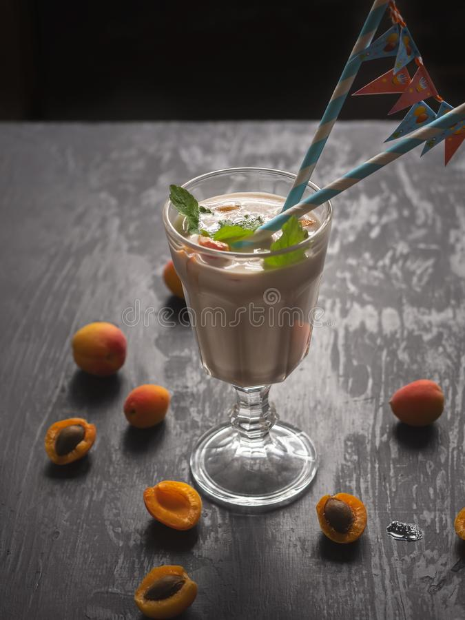 Thick milkshake with fruit, apricots and banana in a large glass goblet. Paper tubes with flags for a bright festive day royalty free stock photography