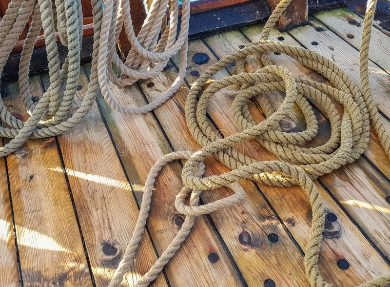 Thick old ropes on the wooden deck of the ship.  royalty free stock image