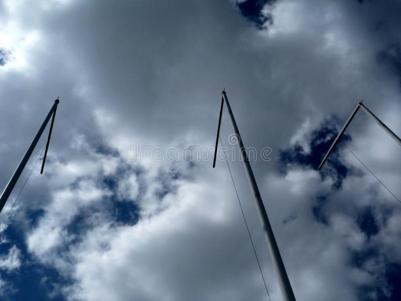 aluminum flag poles in diminishing perspective view. Empty aluminum flag poles in abstract diminishing perspective view with dramatic blue sky above with white stock image