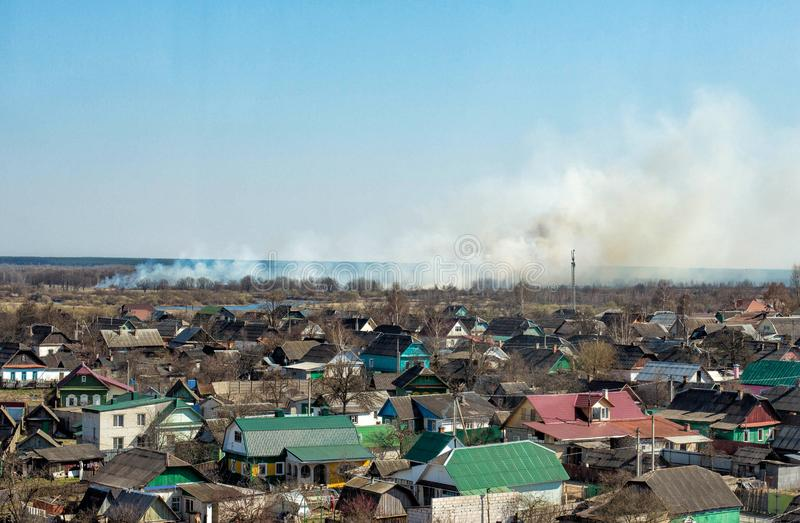 Thick pillar of smoke against a blue sky from forest fires and burning dry grass, copy space. Damage royalty free stock photography