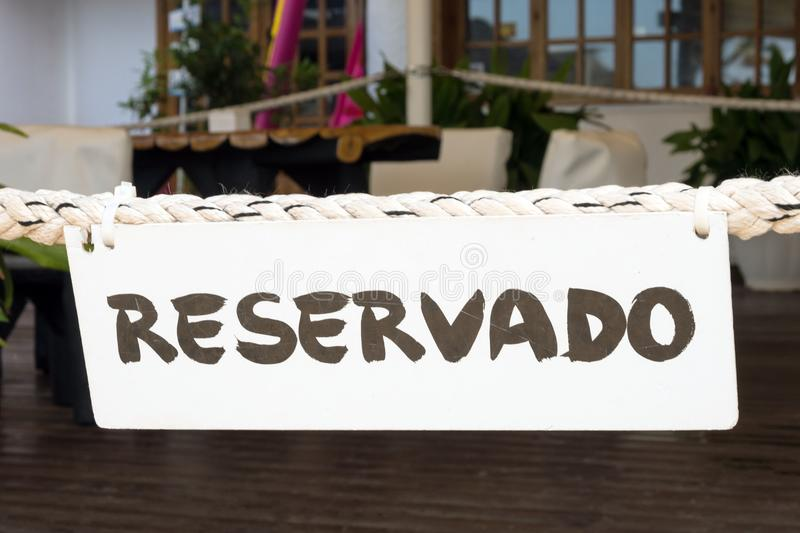 On a thick rope in a Spanish restaurant on the island of Mallorca is a white Reservado sign. stock images