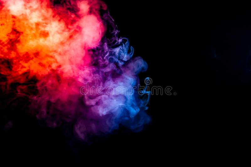 Thick smoke exhaled from a vape, highlighted by a blue-violet orange color like a flame an explosion against a black background, stock photo