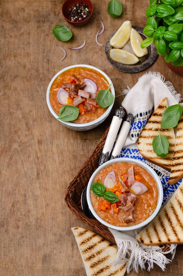 Thick soup with lentils, slices of meat and vegetables. In a dish on a wooden background. Selective focus stock photos