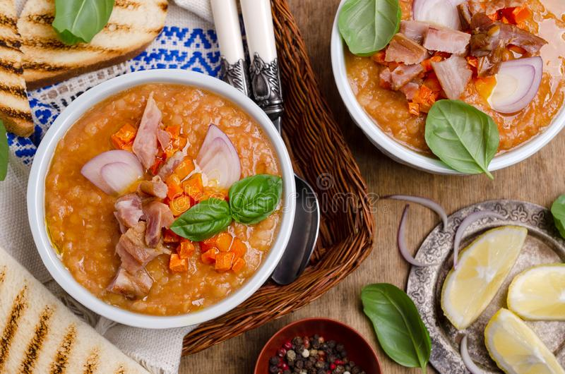 Thick soup with lentils, slices of meat and vegetables. In a dish on a wooden background. Selective focus royalty free stock image