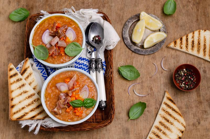 Thick soup with lentils, slices of meat and vegetables. In a dish on a wooden background. Selective focus royalty free stock photo