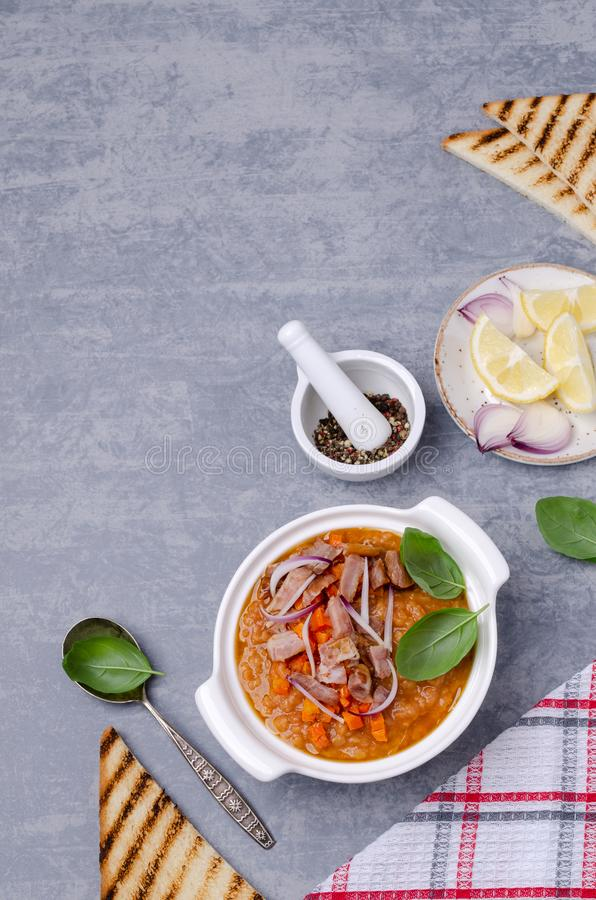 Thick soup with lentils, slices of meat and vegetables. In a dish on a wooden background. Selective focus royalty free stock images