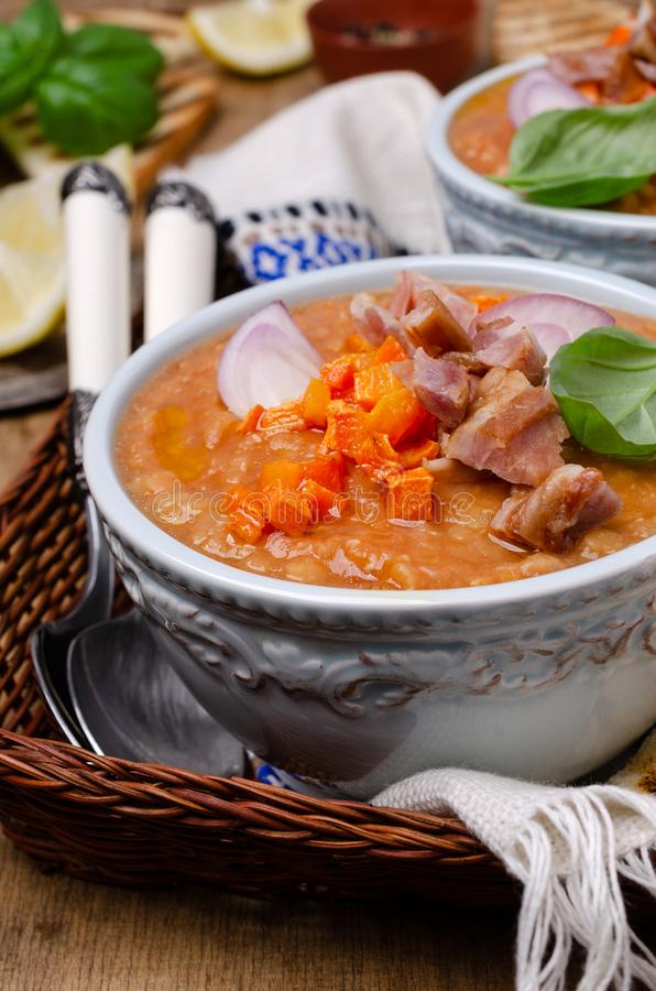 Thick soup with lentils, slices of meat and vegetables. In a dish on a wooden background. Selective focus stock image