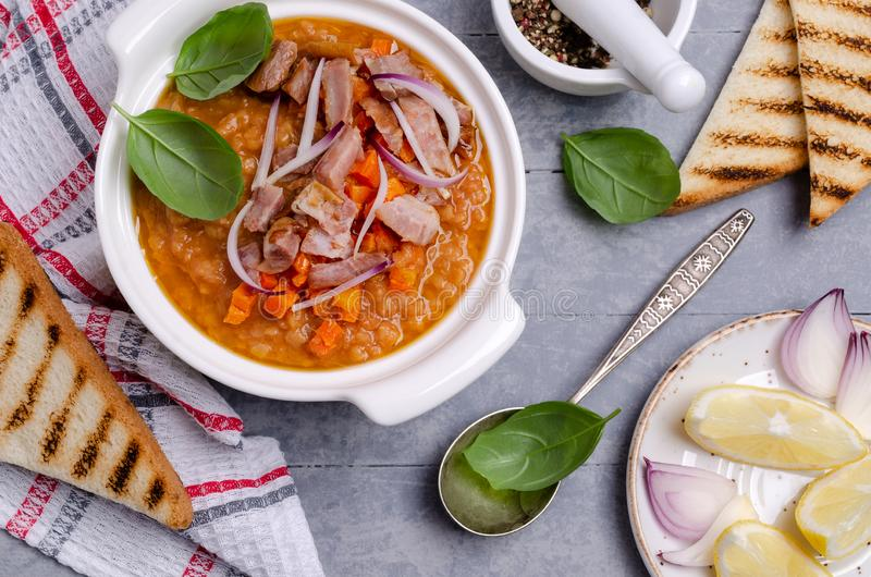 Thick soup with lentils, slices of meat and vegetables. In a dish on a wooden background. Selective focus stock images
