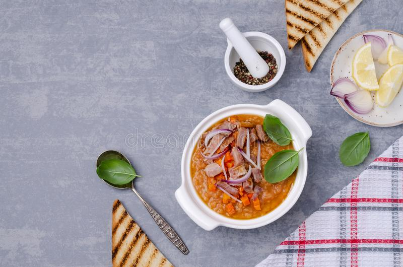Thick soup with lentils, slices of meat and vegetables. In a dish on a wooden background. Selective focus stock photography