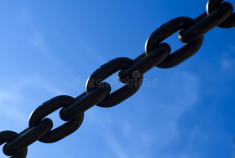 Thick steel chain. Short section of a thick steel chain against blue sky stock photos