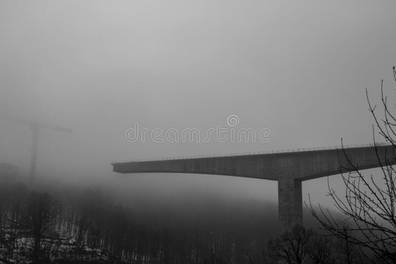 Thick winter fog and bridge construction stock images