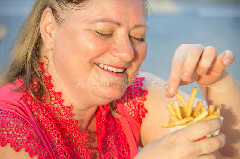 Thick woman eating fast food hamburger and french fries in a cafe at a table on a summer street. Thick woman in red clothes eating fast food hamburger and french royalty free stock images