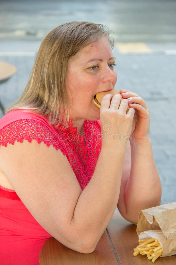 Thick woman eating fast food hamburger and french fries in a cafe at a table on a summer street. Thick woman in red clothes eating fast food hamburger and french stock image