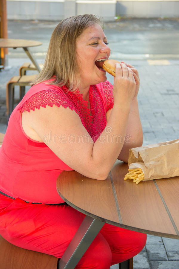 Thick woman eating fast food hamburger and french fries in a cafe at a table on a summer street. Thick woman in red clothes eating fast food hamburger and french stock photos