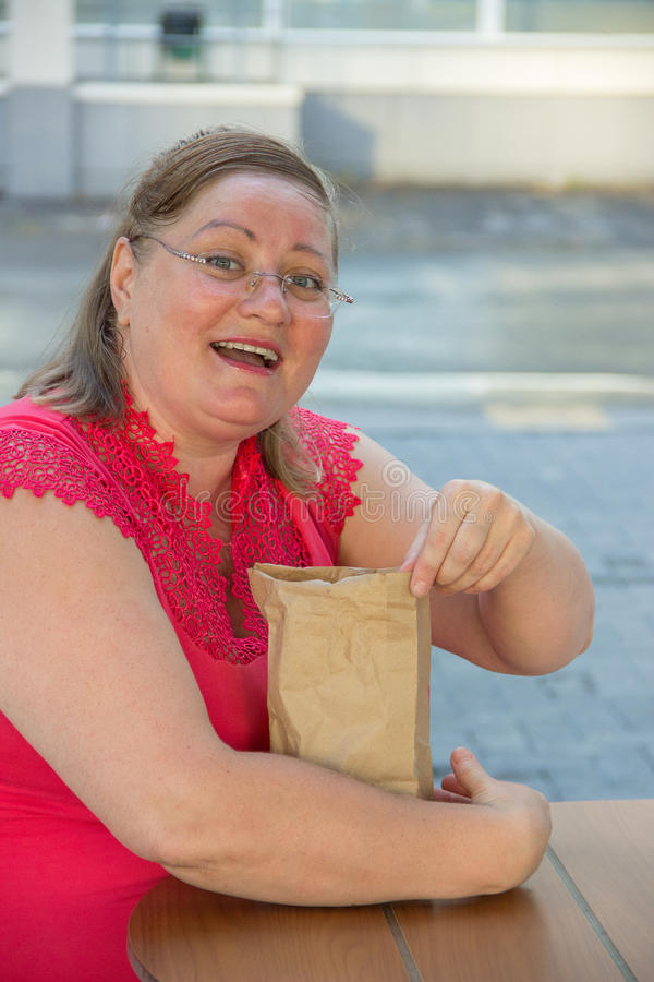 Thick woman eating fast food hamburger and french fries in a cafe at a table on a summer street. Thick woman in red clothes eating fast food hamburger and french stock images