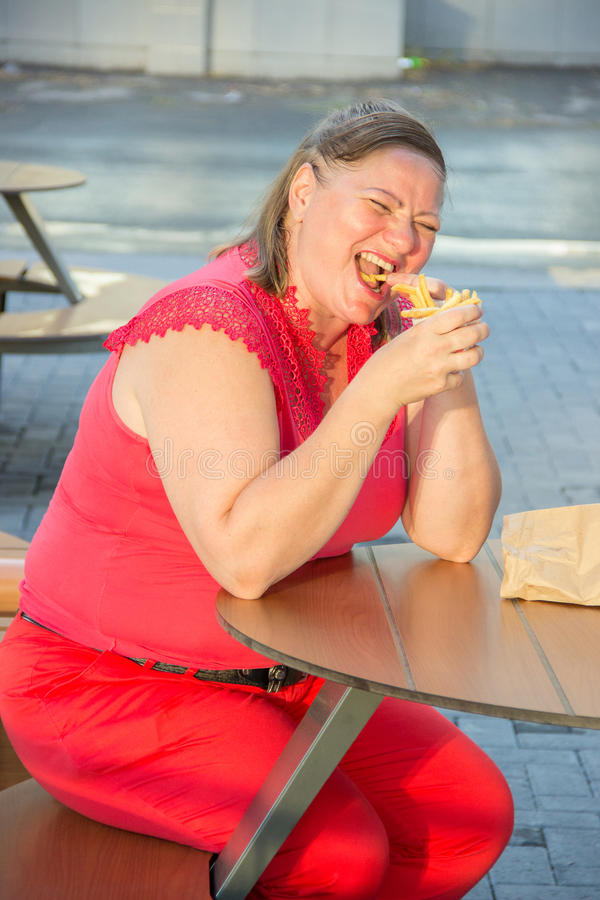 Thick woman eating fast food hamburger and french fries in a cafe at a table on a summer street. Thick woman in red clothes eating fast food hamburger and french royalty free stock photo