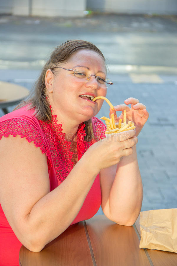 Thick woman eating fast food hamburger and french fries in a cafe. Thick woman in red clothes eating fast food hamburger and french fries in a cafe at a table on stock images
