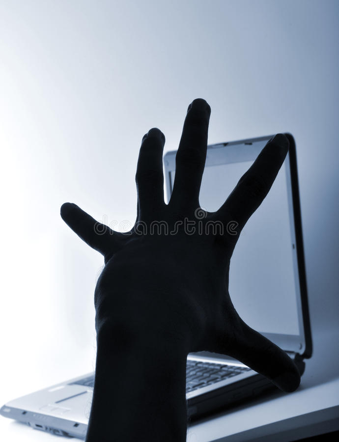Cyber crime. Thief hand ready to hack the computer stock photos
