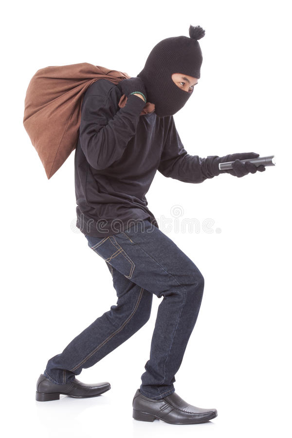 Thief with bag and holding flashlight stock photo