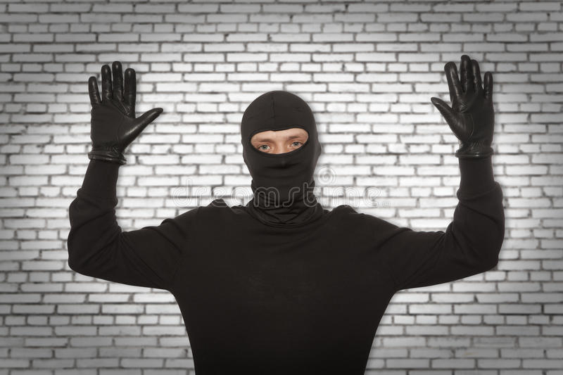 Thief with balaclava. Caught in front of the wall stock photo