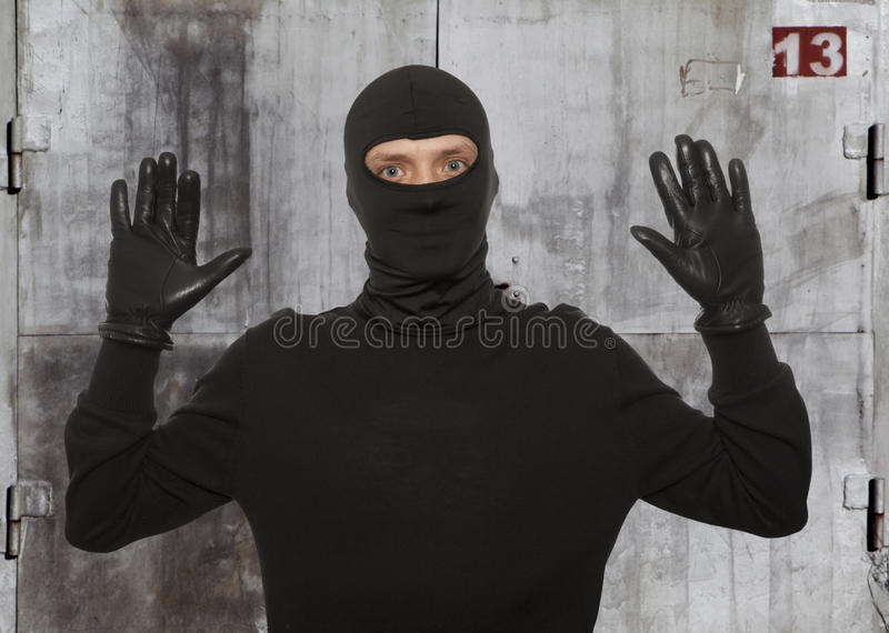 Thief with balaclava. Caught in front of the wall royalty free stock image