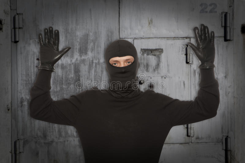 Thief with balaclava. Caught in front of the wall royalty free stock photos