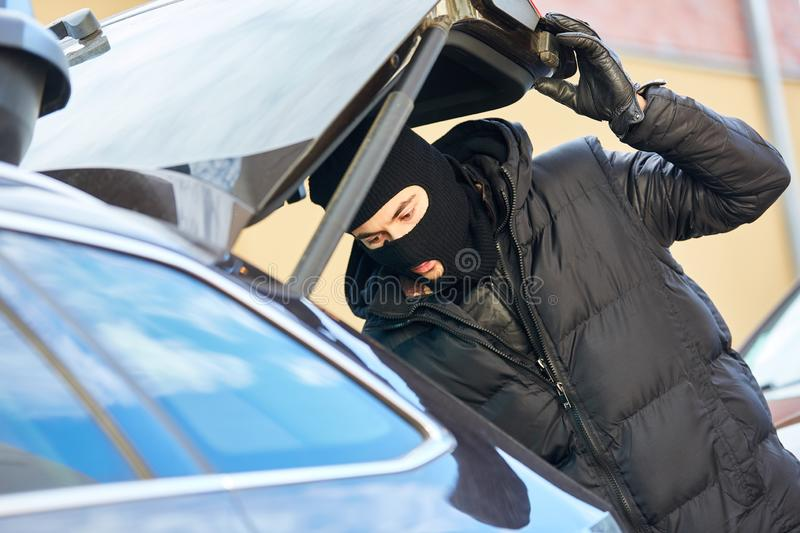 Thief opens car door of car. Thief with balaclava opens Koffferraum of a car royalty free stock photos