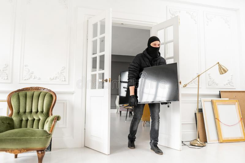 Thief with black balaclava stealing modern expensive television. Luxury apartment with stucco. Man burglar stealing tv. Set from house stock images