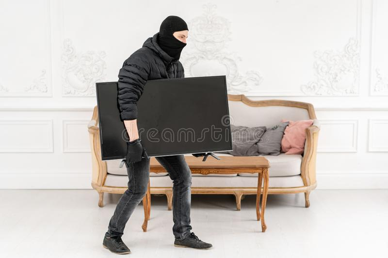 Thief with black balaclava stealing modern expensive television. Luxury apartment with stucco. Man burglar stealing tv. Set from house stock image