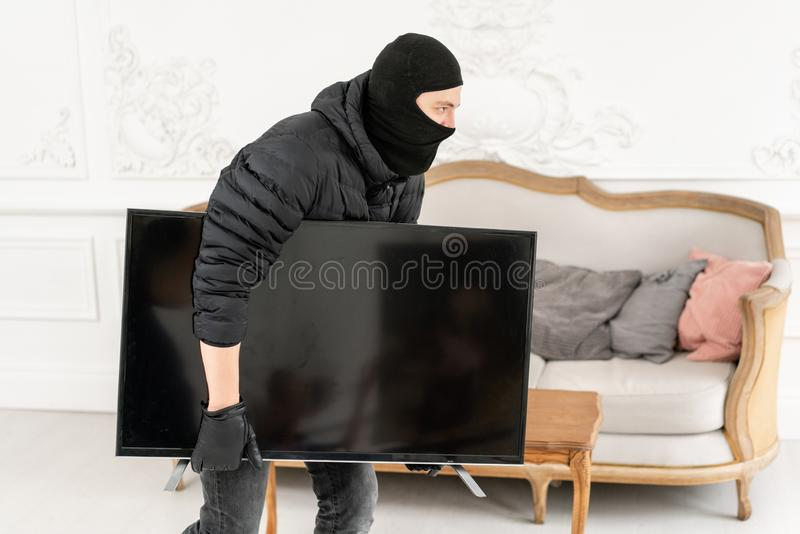 Thief with black balaclava stealing modern expensive television. Luxury apartment with stucco. Man burglar stealing tv. Set from house stock photo