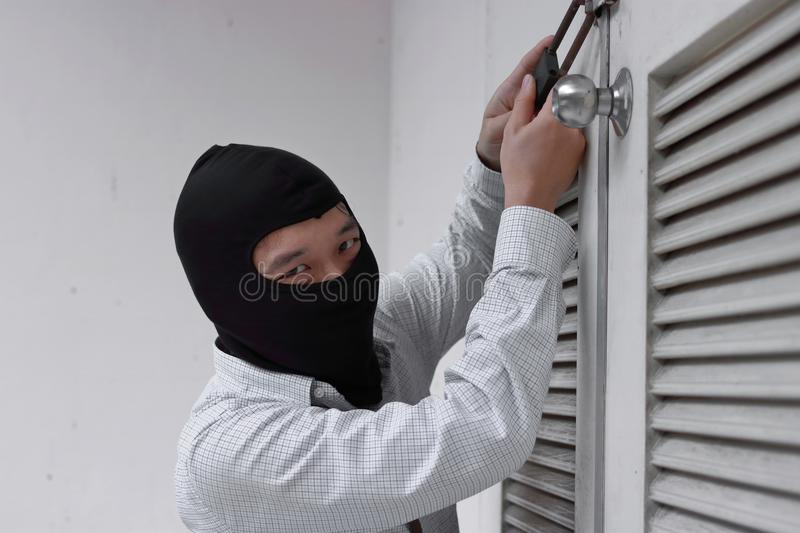 Thief in black balaclava trying to break into house royalty free stock photo