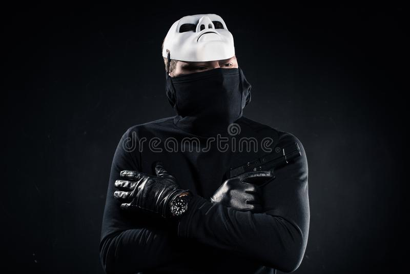 Thief in black balaclava and white mask holding gun in folded arms. On black stock photos