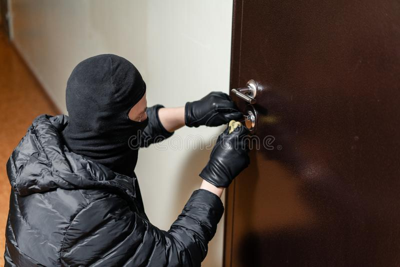 Thief in black mask trying to pick lock a door. House thief concept. stock photos