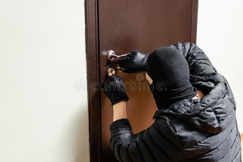 Thief in black mask trying to pick lock a door. House thief concept. Thief in black mask trying to pick lock a door. House thief concept royalty free stock image
