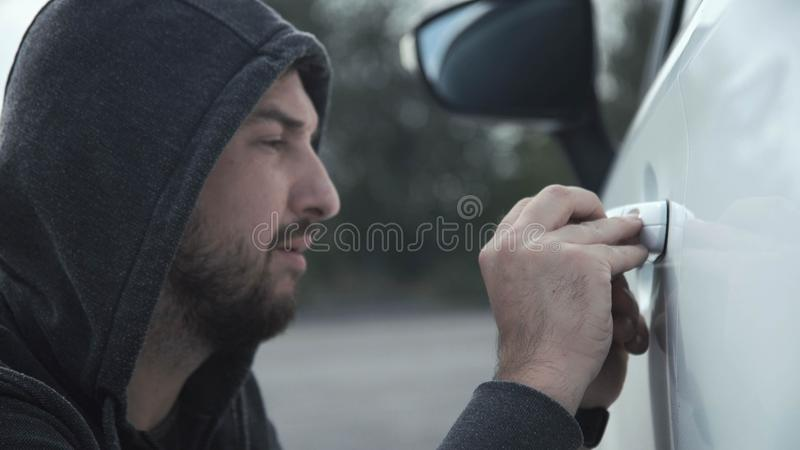 The thief breaks the car. The thief wearing hoodie breaks the car door with a metal tool takes bag and gone stock photo