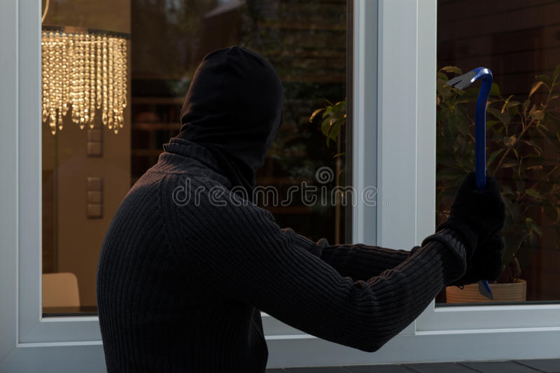 Thief breaks the glass stock photo