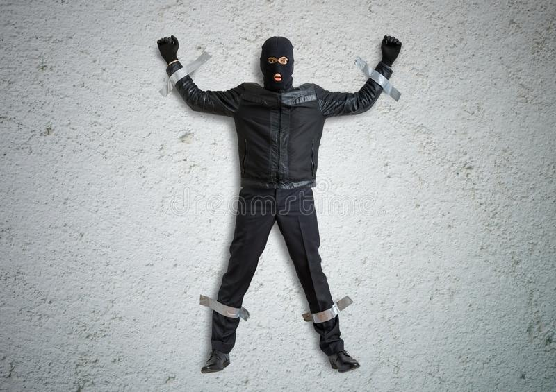 Thief or burglar masked with balaclava is caught and is taped to the wall with duct tape. stock images