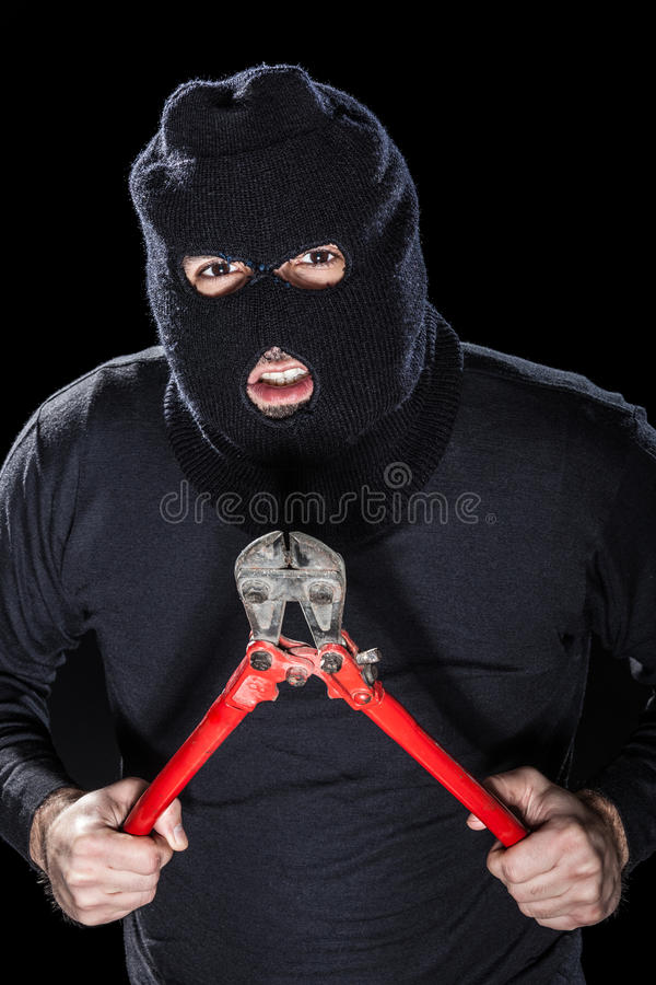 Thief. A burglar wearing a balaclava holding huge wire cutters over black background stock photos
