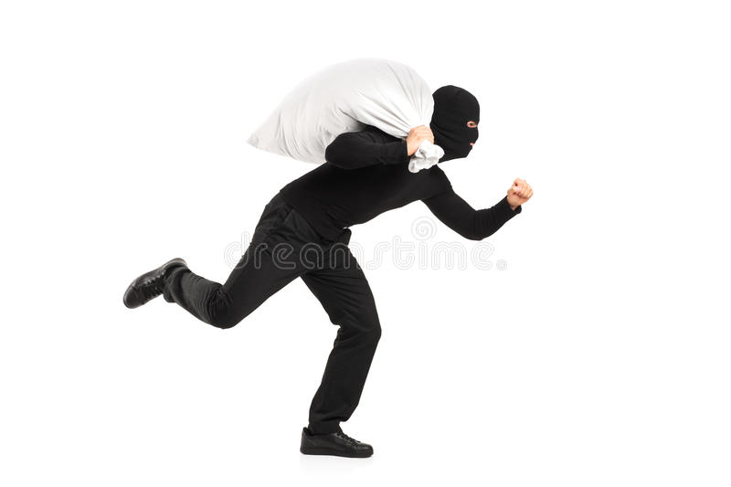 Thief carrying a bag and running away stock photography