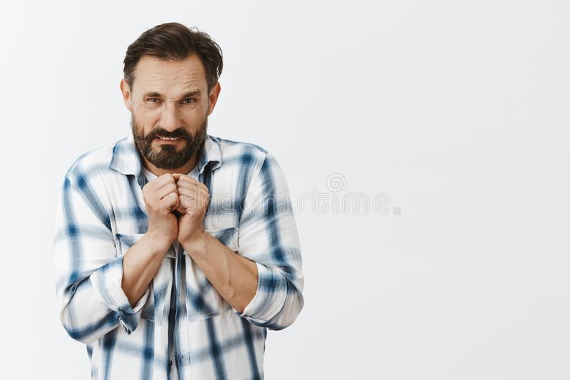 Thief caught by police, feeling angry and displeased. Portrait of mad adult male with beard and dark hair, holding royalty free stock photo