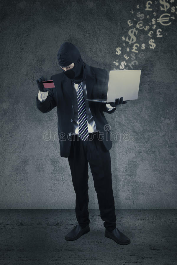 Thief with credit card and laptop royalty free stock image