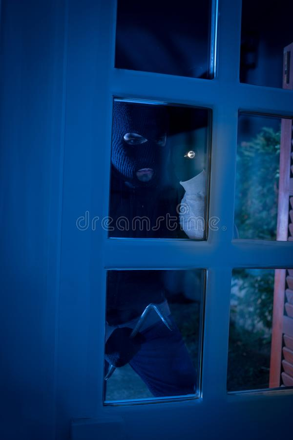 Thief with crowbar breaking into a house royalty free stock image