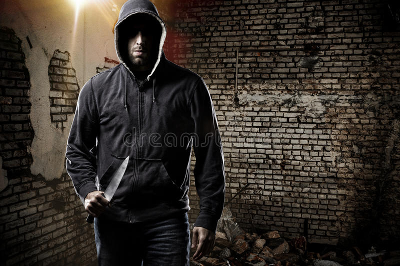 Thief in a dark alley. Thief in the hood on a dark alley stock images