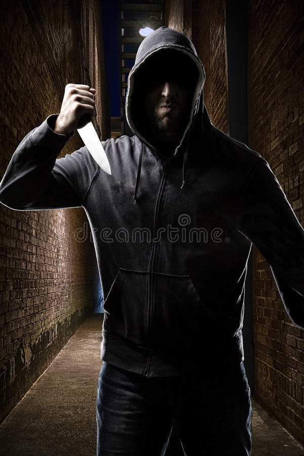 Thief on a dark alley. Thief in the hood on a dark alley stock photos