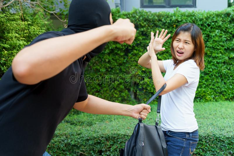 Thief fighting and stealing handbag from screaming asian woman a royalty free stock images