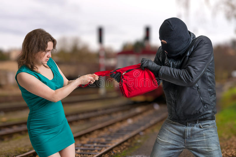 Thief is fighting with woman and stealing handbag stock photo
