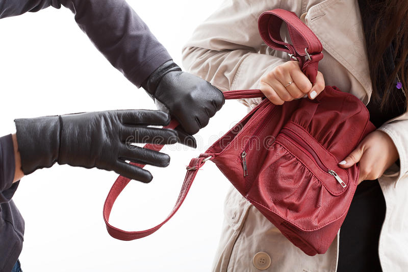 Thief holding a bag. A closeup of a thief wearing gloves holding a woman's bag royalty free stock images